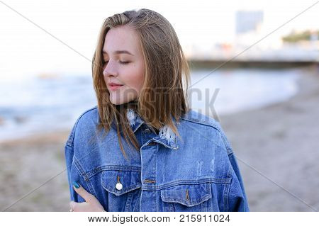 Pretty woman in high spirits looks into camera and smiles sweetly, develops hair in wind with hands and enjoys noise of surf and sea smell, standing on beach of sandy beach on warm summer evening at sunset. Woman of European appearance with blond mid-leng