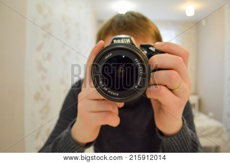 The man is taking pictures of himself the lens is close-up. The man covers his face with the camera's lens. Belarus. 22.11.2017.