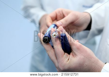 Insulin cartridge and ampoule in the hands of a doctor. The doctor shows the ampoule of insulin to the patient. Insulin cartridge in the hands of a man.