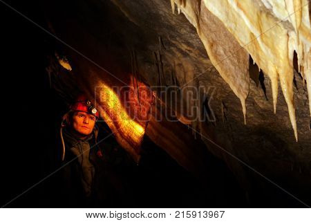 Spelunker wondering in a beautiful cave with stalactites