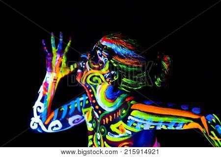 An attractive young girl in bright blacklight bodyart glowing in darkness poster