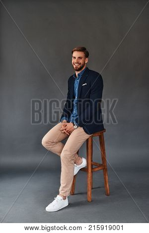 Amazing look! Full length of handsome young smiling man looking at camera while sitting on stool against grey background
