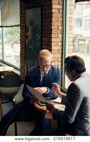 Coworkers discussing business report at meeting in cafe