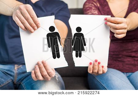 Break up divorce and marital problems concept. Couple holding ripped pieces of paper with man and woman symbol.