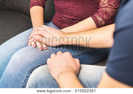 Boyfriend apologize to girlfriend. Couple support each other. Comforting or telling bad news. Young man holding hand and comforting woman. Apology and forgiveness concept.