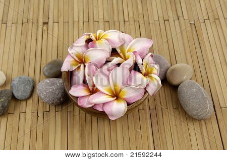 frangipani flower in bowl with stones on bamboo mat