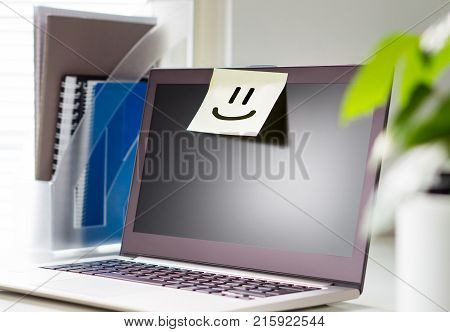 Good working environment and happy atmosphere in workplace. Team spirit. Smiley face drawn on a sticky paper and post it note on laptop in office workstation.