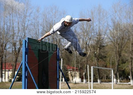 Belarus the city of Gomel 12.04.2017. Open lesson on fire fighting.Jump over the obstacle course.The athlete jumps over the barrier.Physical education lesson.