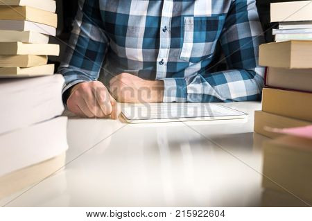 Man reading electronic book or online news with reader. Book in tablet or smart mobile device surrounded by stacks of books.