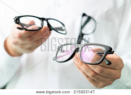 Optician Comparing Lenses Or Showing Customer Different Options In Spectacles. Eye Doctor Showing Ne
