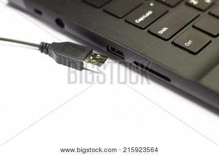Closeup - USB cable connect to USB slot on laptop on white table