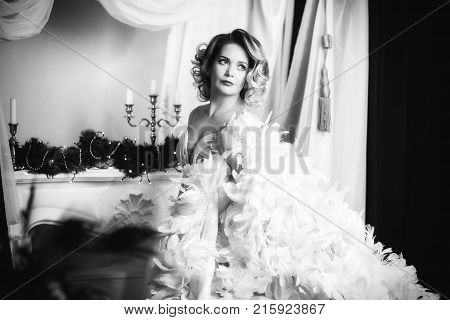 blonde in white feather boa. Horizontal monochrome frame on a light background