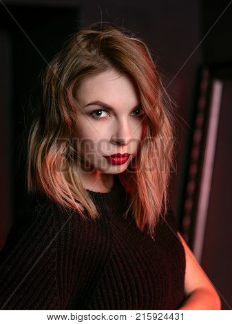 Portrait of the young attractive stylish blonde woman in short dress, knee-high boots and black jacket in the minimalistic room with dark walls in photo studio