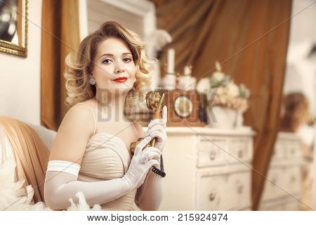 a girl in a beautiful dress and a feather boa speaks on an old telephone. horizontal shot. Style of the 20's, 30's