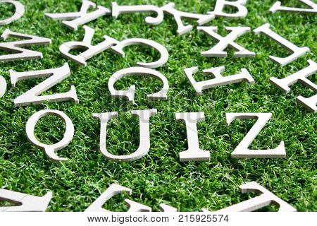 Wood alphabet in wording quiz on artificial green grass background