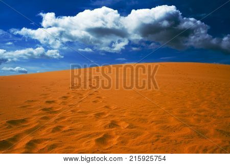 Bright yellow sand empties against the blue sky with clouds. The arid region of the planet