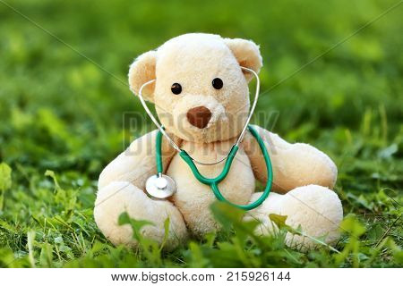 Teddy bear with stethoscope outdoors. Pediatrician concept
