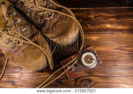 Touristic Magnetic Compass And Boots On Wooden Table