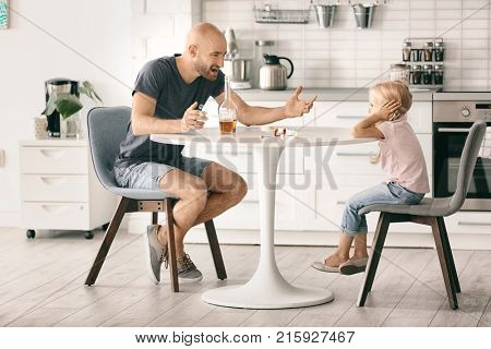 Man drinking alcohol and scolding little girl in kitchen