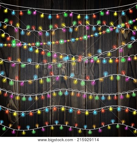 Set of color garland lights. Glowing christmas lights on wooden background. Realistic luminous garland. Includes 10 vector brushes festive strands of Christmas lights
