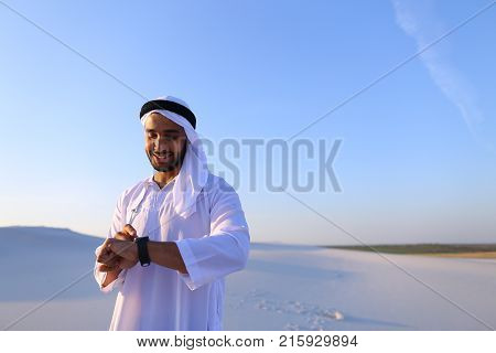 Attractive guy, emirate businessman who put on hand, smiling and examining landscapes of large sandy desert against blue sky on hot summer morning. Swarthy Muslim with short dark hair dressed in kandura, long, sp