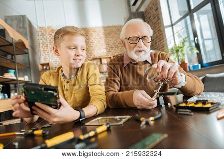 My role model. Positive smart curious boy sitting at the table and looking at his grandfather while trying to be like him