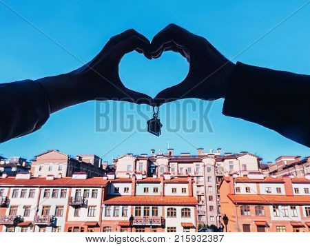 Couple keeps the keys to new housing. hands silhouette holding house keys on house shaped keychain. Male and female hands silhouette heart holding keychain in form of house with key on the background a new buildings.