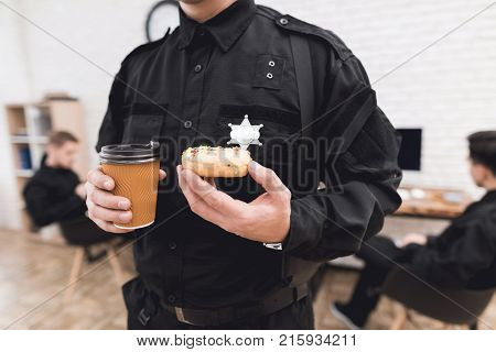 Police officers eat donuts and drink coffee at the police station. They rest in the break of work. They are in a good mood, they are smiling.