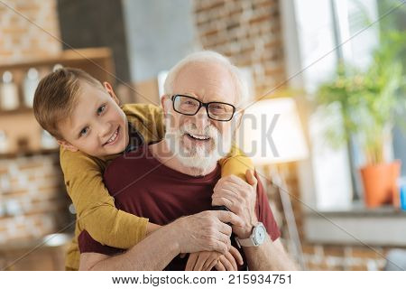 Warm relationships. Joyful nice loving boy standing behind his grandfather and hugging his while expressing his feelings