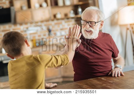 Perfect team. Positive delighted joyful grandfather and grandson smiling and being in a positive mood while giving each other high five