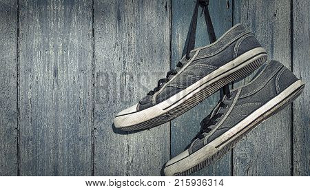 textile torn sneakers hanging from a nail on a background of blue wooden wall empty space on the right