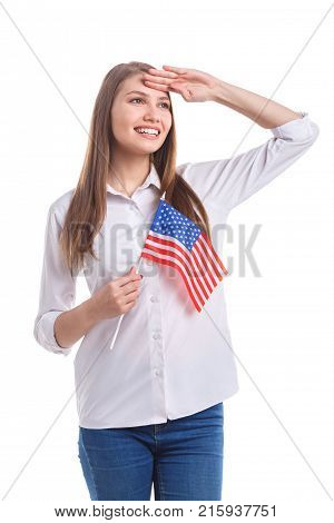 Beautiful girl in white shirt with cute smile salutes with American flag on stick on white isolated background