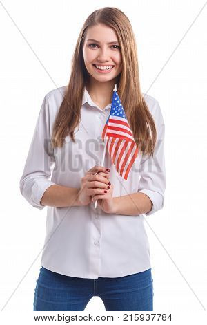 Young girl, with a sweet smile in a white shirt. Holding an American flag on a stick in front of him on a white isolated background