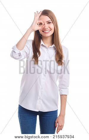 Young, happy woman with a smile in a white shirt made a circle with her fingers and looks through it on a white isolated background