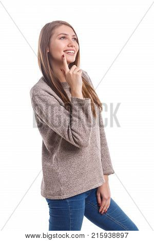 Beautiful, young girl with a cute smile in a sweater dreaming on a white isolated background
