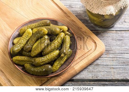 Pickles . Marinated cucumber in plate on wooden background .