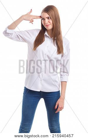 Beautiful girl in white shirt, upset, put her hand to forehead as a gun on white isolated background