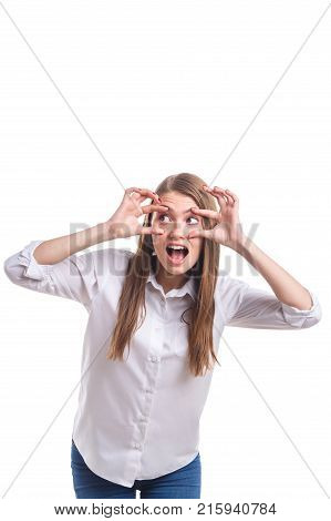 A young and pretty girl in a white shirt is very surprised wide open her eyes with her hands on a white isolated background