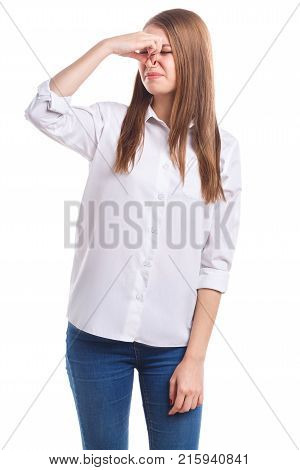A young, beautiful girl in a white shirt covered her nose with an unpleasant odor on a white isolated background
