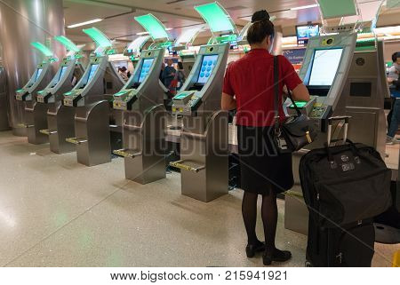 Los Angeles, USA 12, 2017: Young business woman passenger in red dress using custom kiosk for self check and declaration in at LAX Los Angeles International Airport.