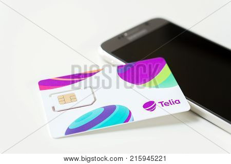 JYVASKYLA FINLAND - JUNE 19 2017: Brand new Telia sim card on smartphone on table. Telia is a telephone company and mobile network operator in Europe. Illustrative editorial.