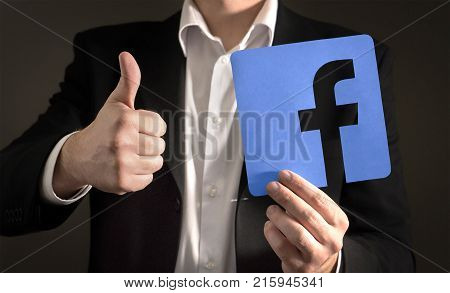 JYVASKYLA FINLAND - JUNE 13 2017: Business man giving thumbs up with a cardboard Facebook logo. Facebook is a popular social media platform launched in 2004. Illustrative editorial.