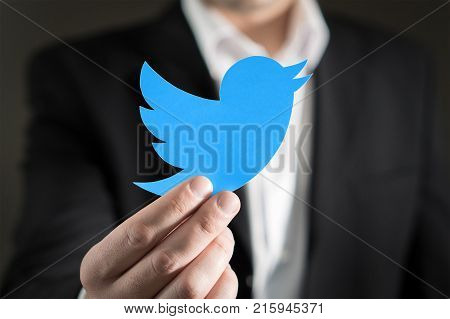 JYVASKYLA FINLAND - JUNE 13 2017: Close up of man in a suit showing printed Twitter logo. Twitter is a social media network that was founded in 2006. Illustrative editorial.