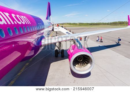 TURKU FINLAND - MAY 22 2017: Passengers boarding to Wizzair airplane from back door stairs behind wing. Wizzair is a Hungarian low cost airline. In Finland it flies from Turku to Gdansk.