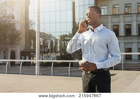 Serious black businessman having tough conversation on smartphone outdoors. Young african-american salesman talking with client near business centre in urban area cityscape