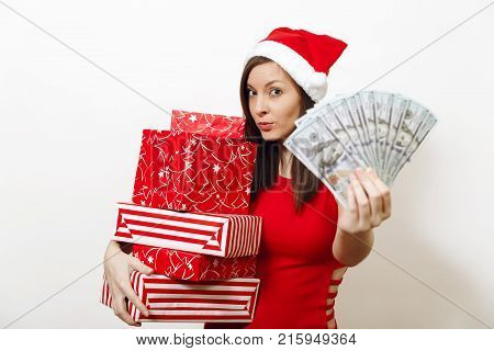 Pretty caucasian young happy woman in red dress and Christmas hat holding gift boxes and money banknotes on white background. Santa girl with present and cash isolated. New Year holiday 2018 concept.