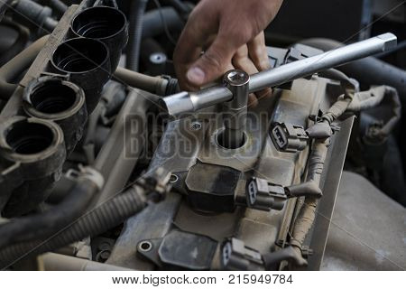Car repair. Ignition system repair. The specialist's hand grasps the socket wrench.
