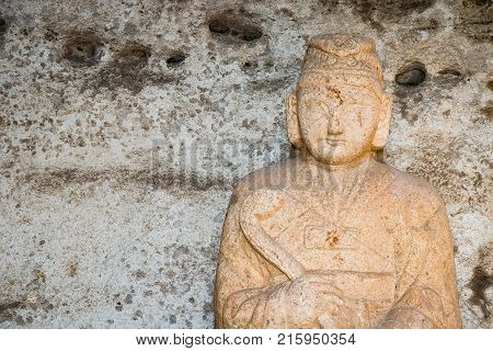 A sculpture of Buddha carved into a beige colored stone