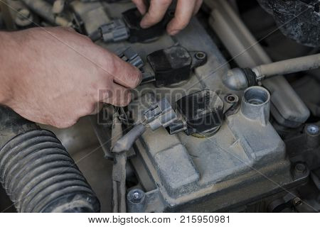 Ignition system check is finished. The mechanic's arms connect the power to the spark plugs.
