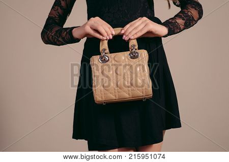 Fashionable woman with a brown bag in her hands and black evening dress.